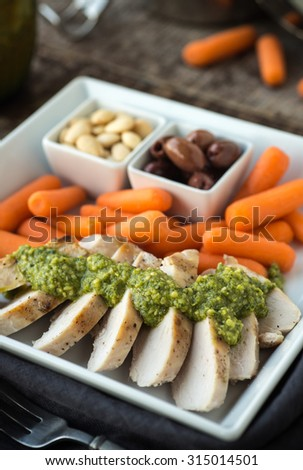 Fresh pesto over grilled chicken with olives carrots and almonds - stock photo