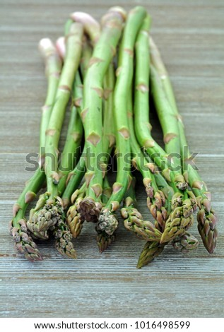 Fresh picked asparagus on rustic background in vertical format shot in natural light