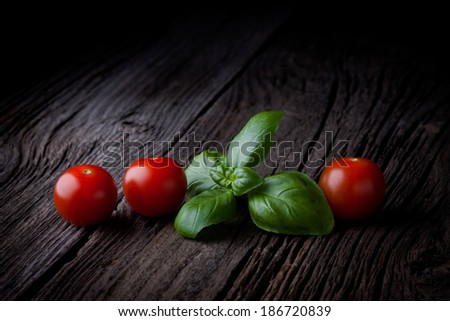 Fresh picked basil leaves and cherry tomatoes composition. Green herbs and vegetables photography taken on rustic old table.