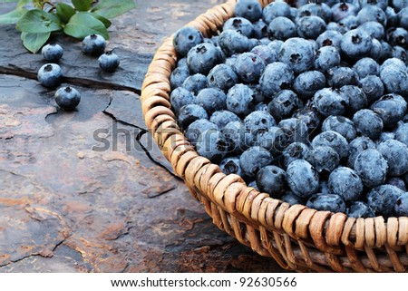 Fresh picked organic blueberries  in a woven basket on a rustic slate background. Shallow depth of field.