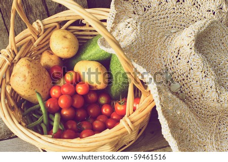Fresh picked organic vegetables and a straw hat on a grunge wood background. - stock photo