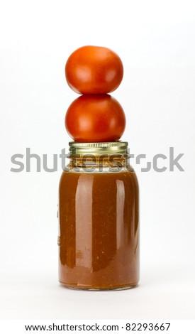 Fresh picked tomatoes stacked on a mason jar of homemade tomato sauce - stock photo