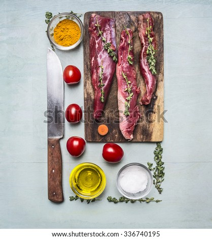 fresh pieces of raw lamb on a chopping board, with herbs, spices, cherry tomatoes, lined rectangle on wooden rustic background top view close up - stock photo