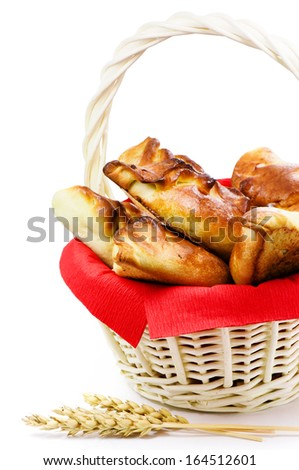 Fresh pies in wattled basket  - stock photo