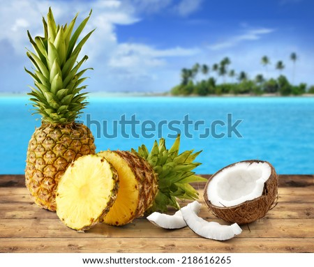 fresh pineapple and coconut in tropical landscape - stock photo