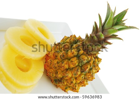 fresh pineapple and slices on white dish