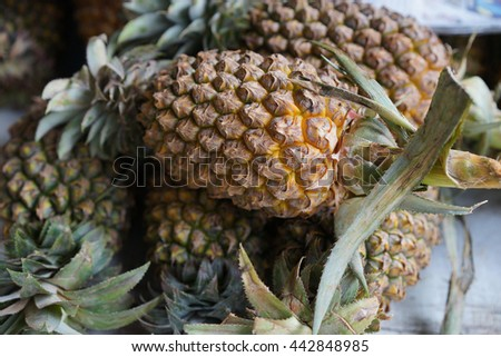 Fresh pineapple at the market with blurred background - stock photo