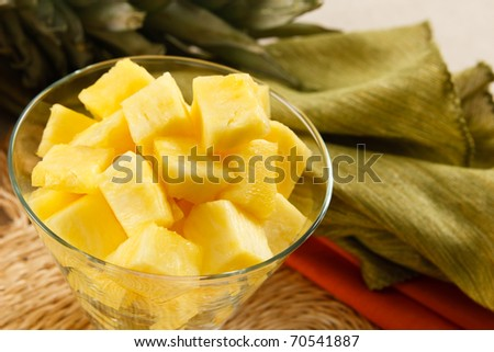 Fresh pineapple chunks served in a contemporary glass bowl - stock photo