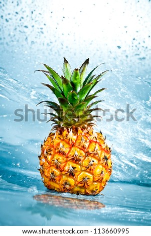 Fresh pineapple in water splashes - stock photo