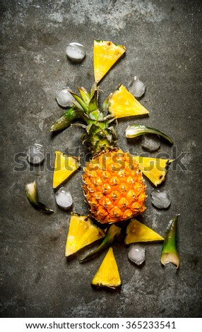 Fresh pineapple with slices and ice . On the stone table. Top view - stock photo