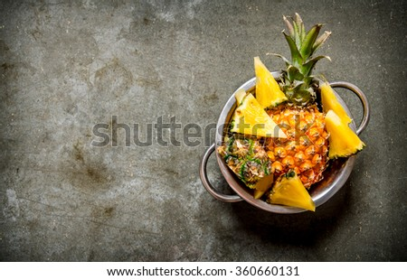 Fresh pineapples in the pan. On the stone table. Free space for text . Top view - stock photo