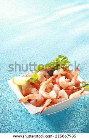 Fresh pink prawn or shrimp appetizer served with sliced lemon and leafy greens for a gourmet shellfish start to a meal, on blue with copyspace - stock photo