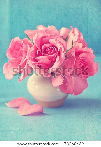 fresh pink roses in a ceramic vase on a blue background - stock photo