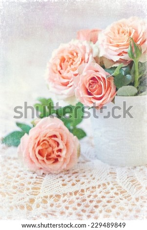 fresh pink roses in a ceramic vase on a table.  - stock photo