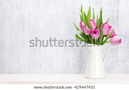 Fresh pink tulip flowers bouquet on shelf in front of wooden wall. View with copy space - stock photo