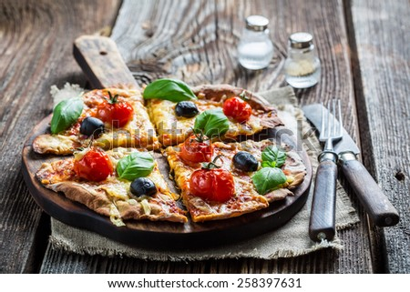 Fresh pizza on paper and old wooden table - stock photo