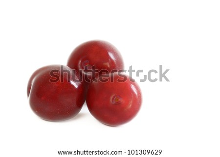 Fresh plum fruits with green leaf isolated on white background