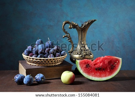 Fresh plums and watermelon on the table - stock photo