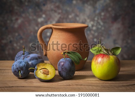 Fresh plums, apples and a ceramic carafe on the table - stock photo