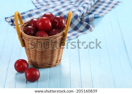 Fresh plums in a wicker basket on a background of colored boards - stock photo