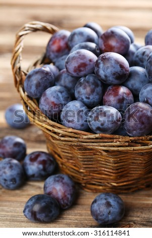 Fresh plums in basket on the brown wooden background - stock photo
