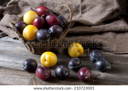 Fresh plums in basket on wooden board - stock photo