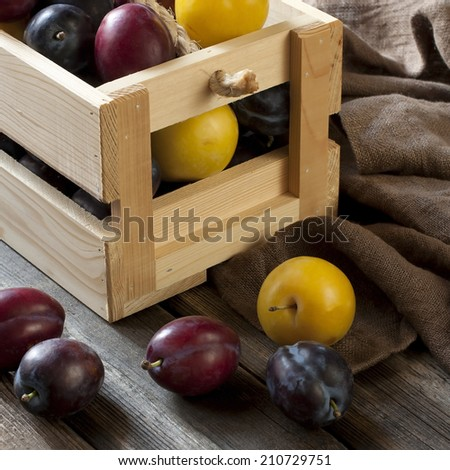 Fresh plums in box on wooden board - stock photo
