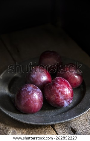 Fresh plums in natural light setting with moody vintage style - stock photo