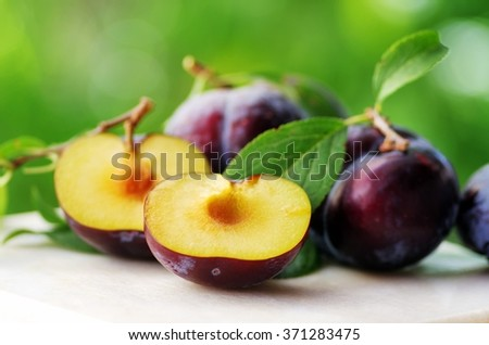 Fresh plums isolated on table - stock photo