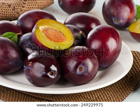 Fresh plums on a white plate, Selective focus - stock photo