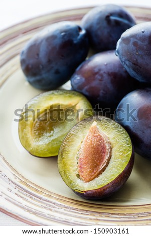 Fresh plums on plate over wooden background, closeup, selective focus - stock photo