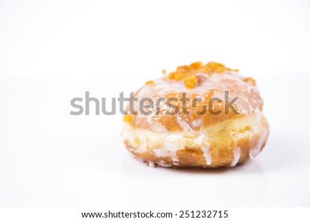 Fresh polish donut with jam, orange peel and icing isolated on white background - stock photo