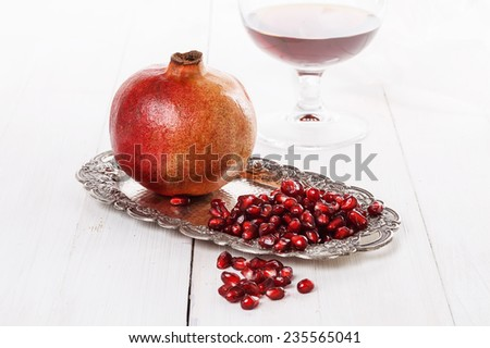 Fresh pomegranate and pomegranate seeds on a vintage silver plate on a white wooden table - stock photo