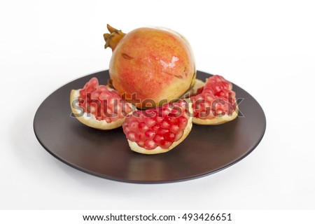 Fresh pomegranate on black plate and white background.