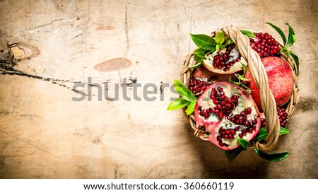 Fresh pomegranates in a basket with leaves. On a wooden table. Free space for text . Top view - stock photo