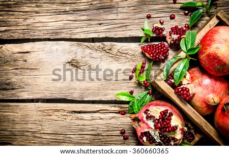 Fresh pomegranates in an old box with leaves. On wooden background. Free space for text . Top view - stock photo