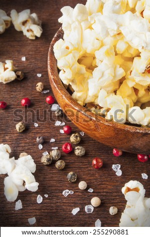 Fresh popcorn in bowl on wooden table