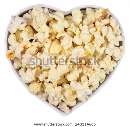Fresh popcorn in plate in the form of heart on a white background - stock photo