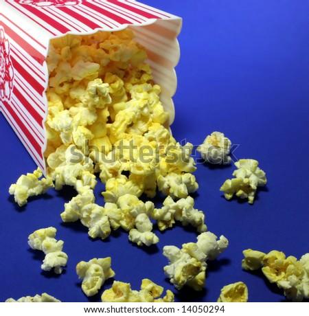 Fresh popcorn spilled on a blue background. - stock photo