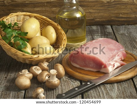 Fresh pork tenderloin with mushrooms, herbs and potatoes - stock photo