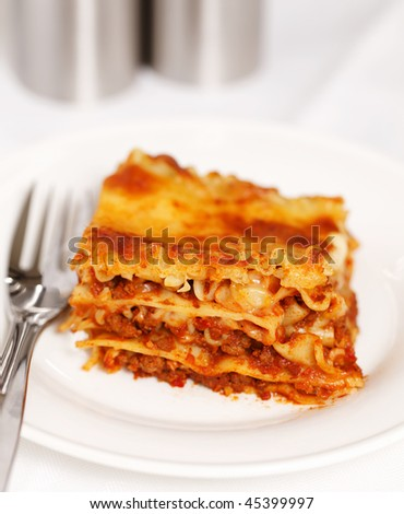 Fresh portion lasagna on a plate with a white background. Very shallow depth of field. - stock photo