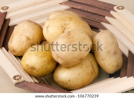 Fresh potatoes in a wooden vase - stock photo