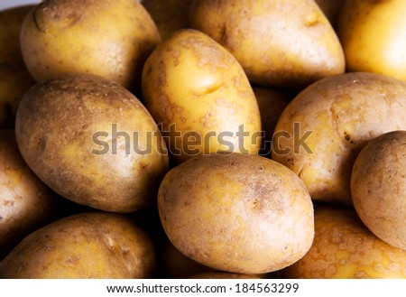 Fresh potatoes.Over wooden background.