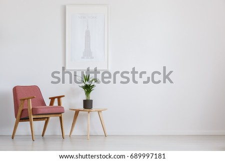 Fresh potted plant placed on table next to pink armchair