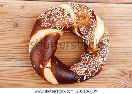 fresh pretzel topped by sesame on wooden table