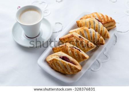 fresh puff pastry with jam on white plate - stock photo