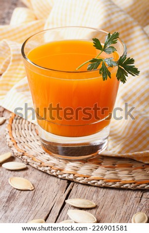 Fresh pumpkin juice in glass close up vertical