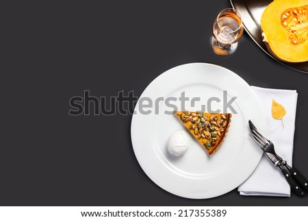 Fresh Pumpkin Pie with whipped cream and pumpkin seeds on white plate over black chalk board. Beautiful autumn Pumpkin thanksgiving pie with copy space  - stock photo