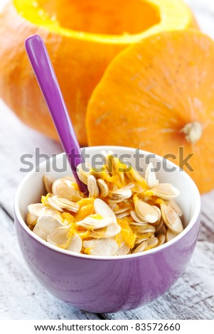 fresh pumpkin seeds in bowl with spoon - stock photo