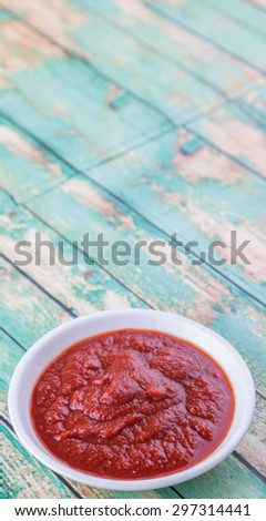 Fresh pureed tomato in white bowl over rustic wooden background - stock photo